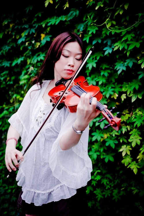 I-Pei Lin playing violin outside in front of ivy.