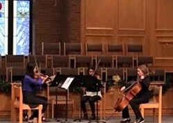 Three student ensemble playing on stage