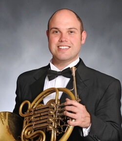 Headshot of Jeffrey holding his french horn