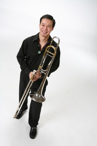 Samuel Chen standing and holding his trombone